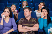Man sitting together with crying women at the cinema — Stock Photo