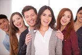 žena s úsměvem, zatímco skupina veselých mladých lidí stojící za ní — Stock fotografie