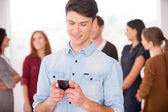 Man holding a mobile phone and smiling — Foto Stock