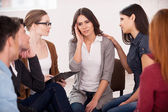Depressed young woman sitting close to other people — Foto Stock