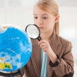 Girl in formalwear examining globe — Photo