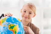 Girl in formalwear examining globe — Stock Photo