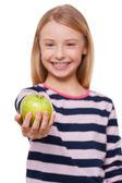 совместное использование apple с вами. жизнерадостная девочка, вытянув руку с зеленым яблоком, стоя, изолированные на белом — Стоковое фото