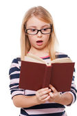 Surprised little girl reading book — Stock Photo