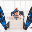 Office worker in snorkel and flippers gesturing sitting at his working place — Stock Photo #41918909