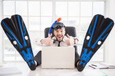 Office worker in snorkel and flippers gesturing sitting at his working place — Stock Photo