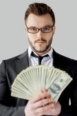 Businessman in glasses holding paper currency and looking at camera — Stock Photo
