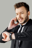 Man in formalwear talking on the phone and checking the time — Stock Photo