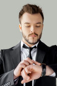 Young man in formalwear checking the time — Stock Photo