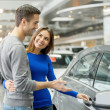 Couple standing at dealership choosing car to buy — Stock Photo #41946811