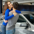 Woman hugging her boyfriend thanks for the new car — Stockfoto