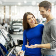 Couple standing at dealership choosing car to buy — Stock Photo #41946819
