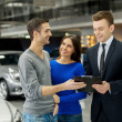 Salesman making deal with young couple — Stock Photo