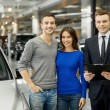 Couple and handsome car salesmstanding at dealership — Stock Photo #41946859