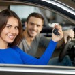 Couple sitting inside of their new car while woman showing keys — Stock Photo #41946939