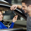 Men standing near the car at the dealership and giving a key to his girlfriend — Foto de Stock
