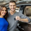 Young men standing near the car, hugging his girlfriend and holding a key — Stock Photo