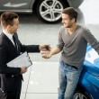 Car salesmmaking deal with customer at dealership — Stock Photo #41947071