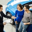 Car salesman telling about the features of the car to the customers — Stock Photo #41947073