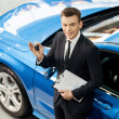 Car salesmstanding at dealership holding key — Stock Photo #41947105