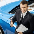Car salesmstanding at dealership holding key — Stock Photo #41947117