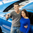 Couple standing near car at dealership and holding key — Stock Photo #41947123