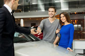 Car salesman giving a key from the new car to the owners — Stock Photo