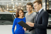 Salesman explaining all the car features to the owners — Stock Photo