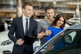Car salesman telling about the features of the car to the customers — Stock Photo
