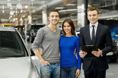 Couple and handsome car salesman standing at the dealership — Stock Photo