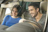 Couple sitting at the front seat of the car checking out the side panel — Stock Photo