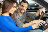 Couple sitting at the front seats of their new car — Stock Photo