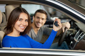Couple sitting inside of their new car while woman showing keys — Stock Photo