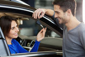 Men standing near the car at the dealership and giving a key to his girlfriend — Stock Photo