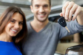 Couple standing near then new car and holding a key — Stock Photo