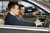 Salesman showing all the car features to the customer — Stock Photo