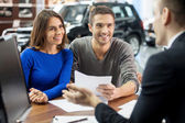 Salesman explaining all the car features to the young attractive owners — Stock Photo