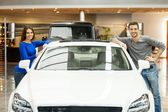 Couple standing at both sides of the car smiling at camera — Stock Photo