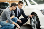 Car salesman showing the advantages of the car to the customer — Stock Photo
