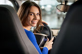 Woman sitting at the front seat of the car looking at camera — Stock Photo