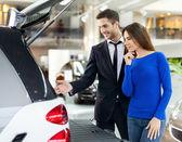 Car salesman showing the car trunk to the customer — Stok fotoğraf