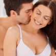 Couple sitting together in bed while man kissing his girlfriend at neck — Stock Photo #41955401