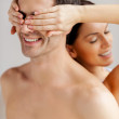 Loving couple standing back to back while woman covering her boyfriend eyes — Stock Photo #41955445