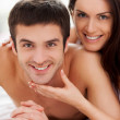 Couple lying in bed and smiling while woman touching her boyfriend chin — Stock Photo #41955489