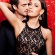 Well-dressed couple posing against red background — Stock Photo