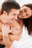 Loving couple having fun while sitting together in bed — Stock Photo
