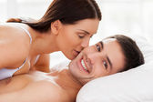 Couple lying in bed while woman kissing her boyfriend at cheek — Stock Photo