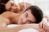 Couple lying in bed and smiling at camera — Stock Photo