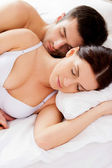 Loving couple sleeping together in bed — Stock Photo