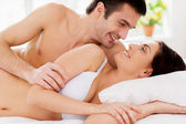 Couple lying in bed and looking at each other with smile — Stock Photo